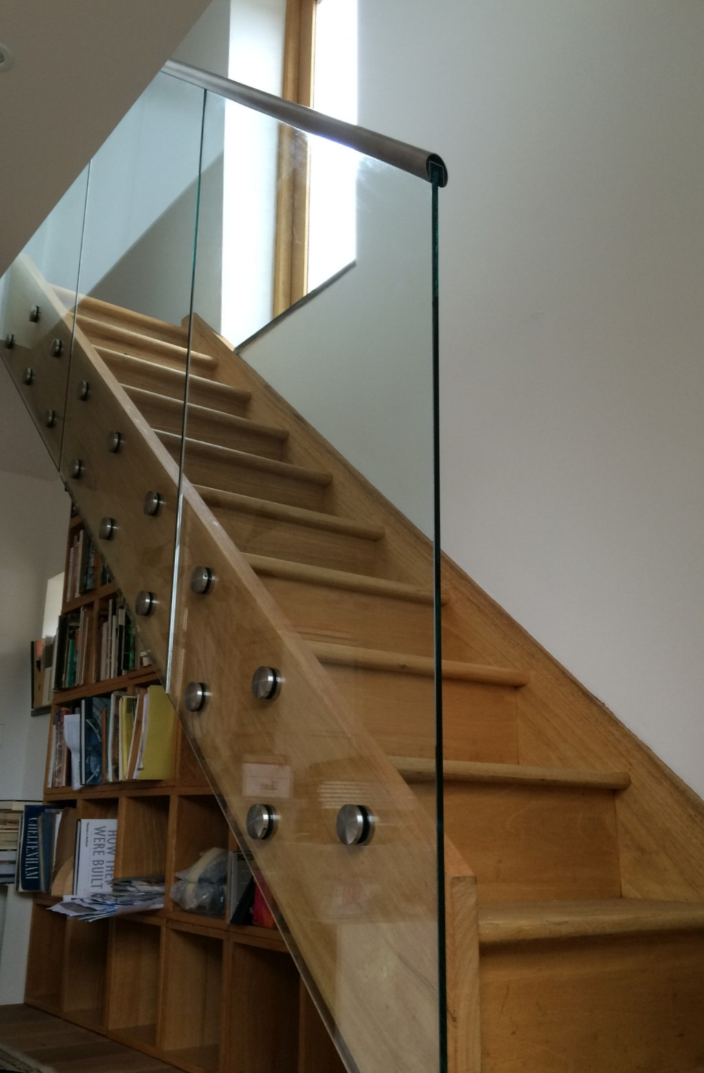 Glass handrail on wooden staircase